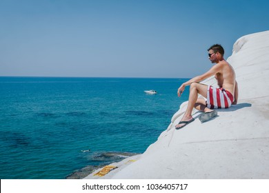 young man at the white beach of Scala dei turch, Famous white marl cliffs at Agrigento, named the turkish steps Scala Dei Turchi in the south of Sicily, Italy in Europe