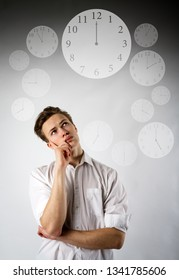 Young man in white and clock. Time is passing. Time concept.