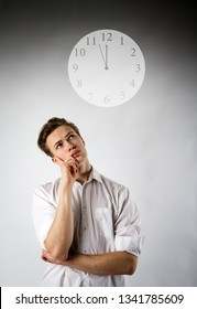 Young man in white and clock. Time concept.