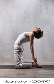 Young man in white clothes practicing yoga. Camel pose. Ustrasana