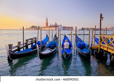 Young man in white clothes sitting in front of Grand Canal in Venice with gondolas against San Giorgio Maggiore church in Italy. Scenery from summer vacation with beautiful colorful morning light.