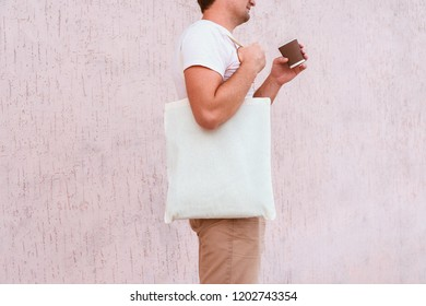 Young man with white cotton bag and paper coffee cup in his hands.