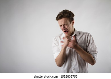 Young man in white is coughing. Pain and Symptoms concept. Infection.