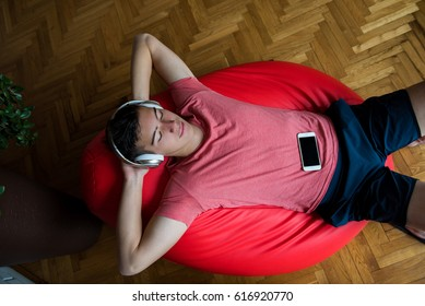 Young man with white headphones and mobile phone resting and listening to music on red lazy bag
