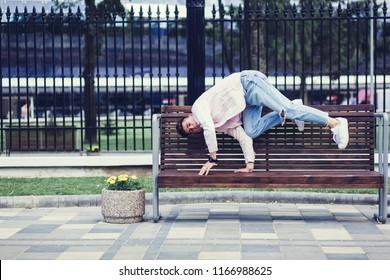 Young man in a white jacket and jeans as break dancer in cityscape