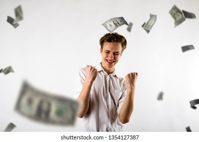 Young man in white is rejoicing. Success and happiness concept. Man in white and dollars.