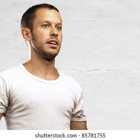 young man with a white shirt against a grunge wall
