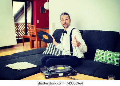 young man in white shirt with bow-tie with old records in his living room