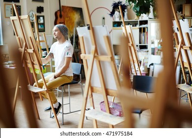 Young man in white shirt covered in paint sitting behind easel sketching on canvas in brightly lit studio