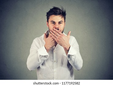 Young man in white shirt covering mouth keeping privacy and speaking no evil