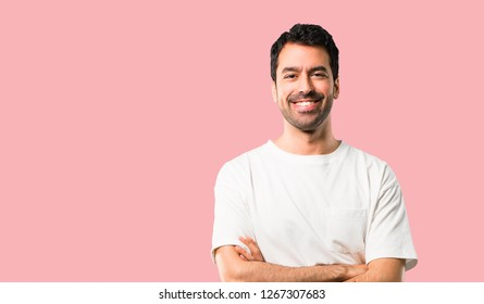 Young man with white shirt keeping the arms crossed in frontal position. Confident expression on isolated pink background