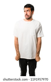 Young man with white shirt is a little bit nervous and scared pressing the teeth on isolated white background