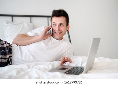 Young man in the white shirt and pajama sitting on a bed looking at the screen holding bank card. Online shopping