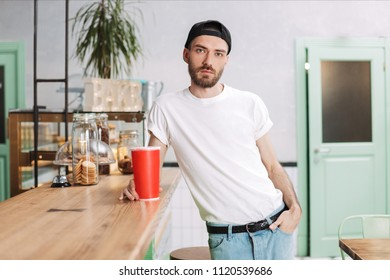 Young man in white t shirt and black cap standing at the bar counter with soda water and dreamily looking in camera in cafe