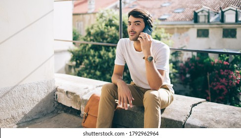 Young man in white t shirt sitting on stone fence of balcony having call on smartphone and looking at camera in sunlight