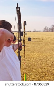 Young man in a white t-shirt aiming loaded bow at target in field