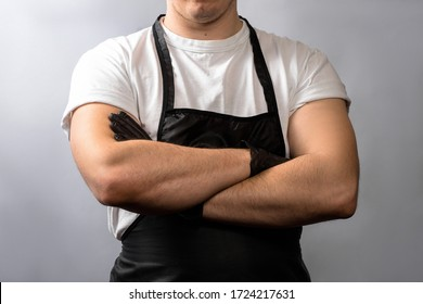 A young man in a white T-shirt with a black apron. crossed arms in black latex gloves on the chest