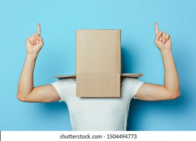 Young man in a white T-shirt with a cardboard box on his head on a blue background. Makes a hand gesture Strength and Power, bodybuilding, sport