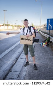 """A young man in a white T-shirt with a large backpack, standing by the road holding a cardboard box with the words """"Anywhere"""" and trying to stop the car on a sunny day. He is trying to hitchhike."""