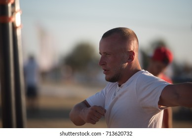 Young man in white t-shirt performing exercises in the street on a summer day. Close-up.