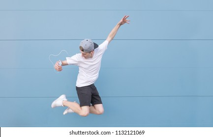 Young man in a white T-shirt and summer clothes listens to music in headphones and jumps on a blue background.Man jumping on the background of a blue wall with headphones and a smartphone in his hands