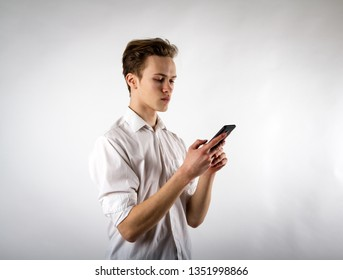 Young man in white using smartphone. Internet correspondence, communication on the Internet.