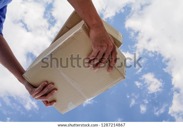 The young man who inspects the goods in the shipping company is checking the parcel and calculating the shipping cost before delivering it to the customer. Audit concept for accuracy before delivery
