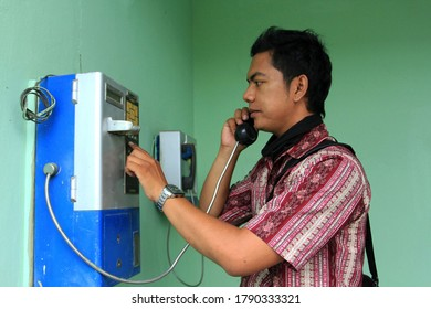 A young man who still uses a payphone that uses coins. Faded green background