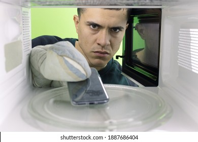 Young man who wants to put his phone in the microwave. Green background for chroma key.