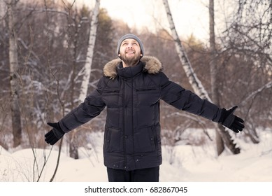 Young man with wide open arms in a winter forest