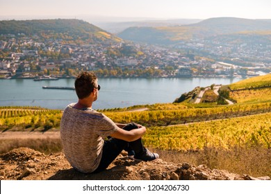 Young man at the wine fields of Rudesheim germany during fall season harvest agriculture