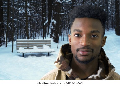 young man in winter snow jacket park trees african