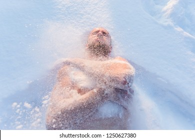 A young man wipes snow after taking a sauna. Cooling steamed body. Spa treatments