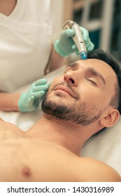 Young man without a shirt lying with closed eyes and professional cosmetologist using modern device for skin nourishing