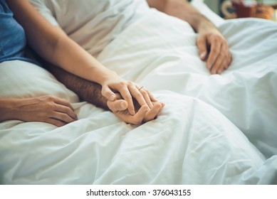 Young man and woman in bed, holding hands