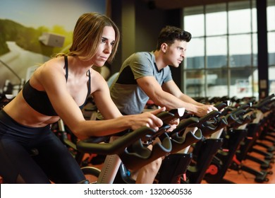 Young man and woman biking in the gym, exercising legs doing cardio workout cycling bikes. Two people in a cyclo indoor class wearing sportswear.