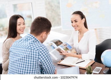 A young man and a woman came to the travel agency. They want to go on a trip during their holidays. The girl agent offers them different countries. She shows it in the booklet.