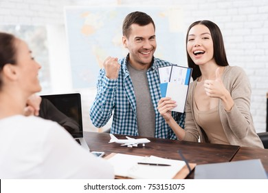 A young man and a woman came to the travel agency. They want to go on a trip during their holidays. The girl agent offers them different countries.