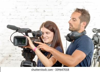 a young man and a young woman cameramen with professional video camera