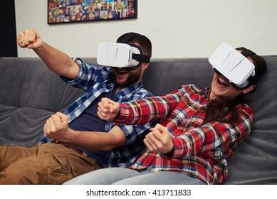 Ein junger Mann und eine junge Frau in ungezwungenen Kleidungsstücken, die mit einem Headset für virtuelle Realität Rennspiele spielen