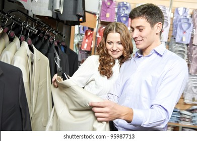 Young man and woman choosing suit jacket during apparel shopping at clothing store