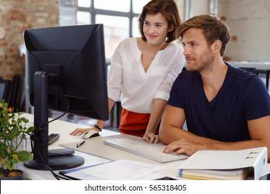 Young man and woman colleagues working together in office looking at computer screen and smiling