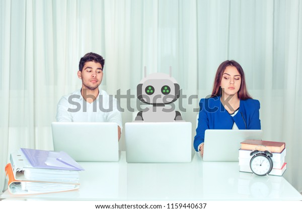 Young man and woman corporate employees with laptops sitting at table with robot colleague and peeking computer being envy about his much effective work being worried to loose jobs. Robot vs human.