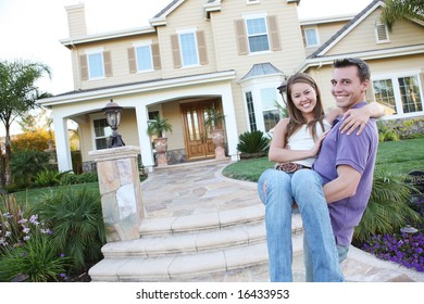 A young man and woman couple in love in front of their new home