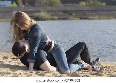 Young man with young woman cuddling on the beach
