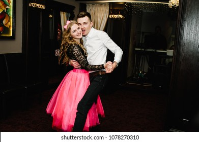 Young man and woman dance in a restaurant. Prince and Princess. Thematic holiday. The guy and girl hug.