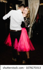 Young man and woman dance in a restaurant. Portrait of Prince and Princess. Thematic holiday. The guy and girl hug.