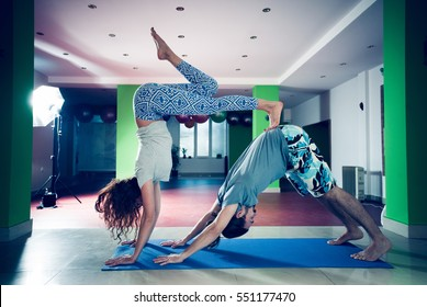 young man and woman doing acro yoga  indoor healthy lifestyle concept