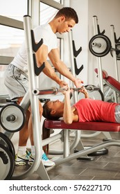 Young man and woman  doing  chest workout on bench press.Assist each other.