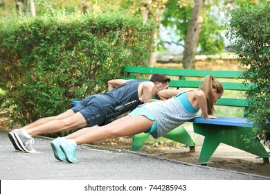 Young man and woman doing exercises in park